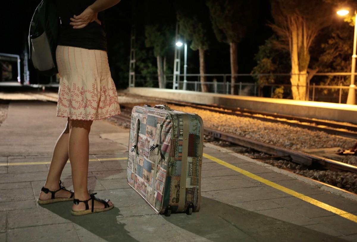 mujer con maleta esperando en estacin